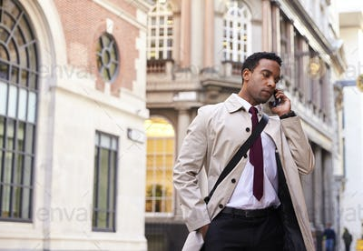 Millennial black businessman standing on a street in London talking on his phone, low angle