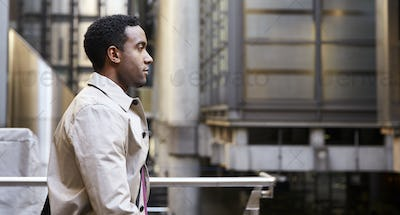 Waist up side view of young black businessman walking in London city
