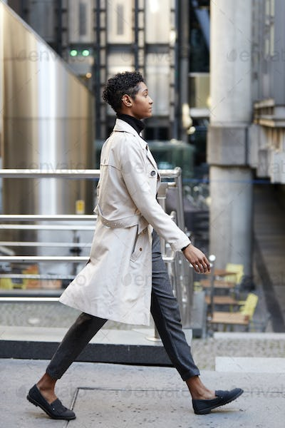 Side view of young black businesswoman walking in the city, London UK, full length