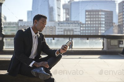 Millennial businessman sitting on the River Thames embankment using smartphone, close up
