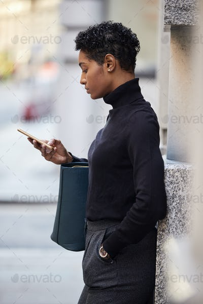 Young black woman standing on a street in London using her smartphone, side view, close up, vertical