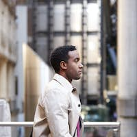 Side view of a young black businessman walking in a street in the city, London UK, close up