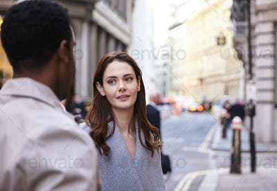 Millennial business colleagues standing on a street in London having a conversation, close up