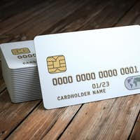 Stack of white blank credit cards mockup on  wooden table backgr