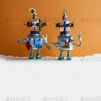 Two glass head robots on brown beige background.