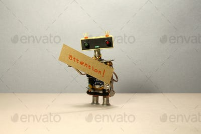The robot is trying to attract attention and concentrate. A clever toy robot holds cardboard