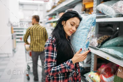 Young couple choosing pillow in supermarket