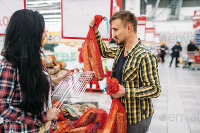 Young couple buying firewood in supermarket