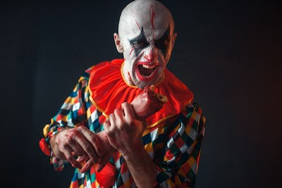 Bloody clown holds human hand, finger in his teeth