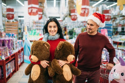Couple with two big plush bears in supermarket