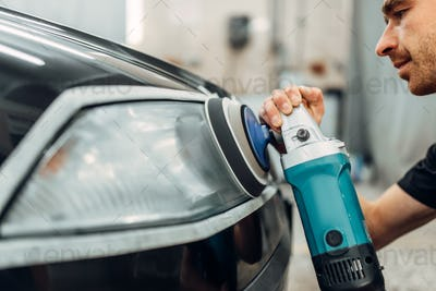 Auto detailing, worker with polishing machine