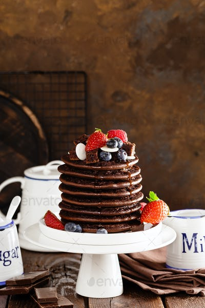 Stack of chocolate pancakes with berries, strawberry, raspberry and blueberry