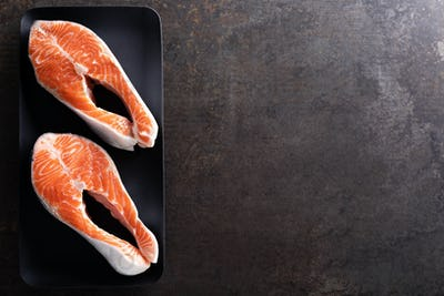 Fresh salmon fish steaks on black background top view