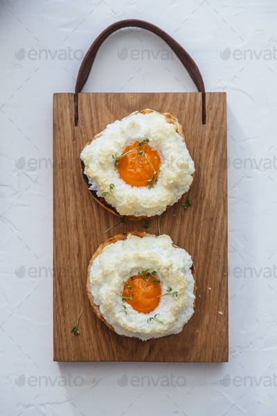 French breakfast with orsini eggs on wooden background, flat lay
