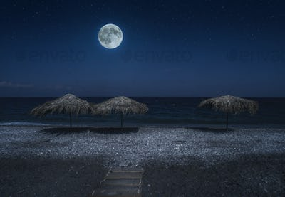 Straw umbrellas on the beach in the night. Moonlight on sea. Nig
