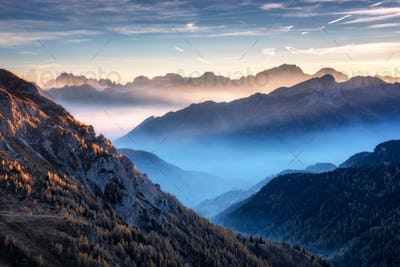 Landscape with alpine mountain valley in low clouds