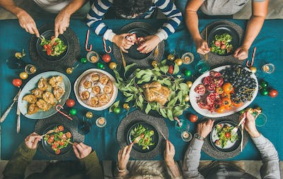 People eating different meals at Christmas party dinner, top view