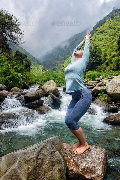 Sorty fit woman doing yoga asana at waterfall