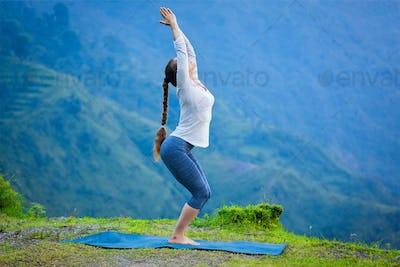 Woman doing yoga asana Utkatasana outdoors