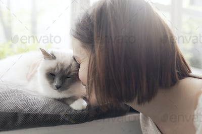 Woman petting her cat next to a window
