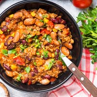 Chili con carne from meat and vegetables on stone table top view.