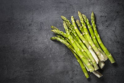 Fresh green asparagus on black slate background.