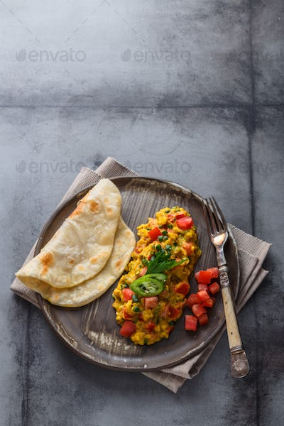 Indian Style scrambled eggs Akuri with paratha, dahl and ice tea, copy space