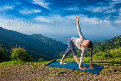 Woman doing Ashtanga Vinyasa yoga asana Parivrtta trikonasana