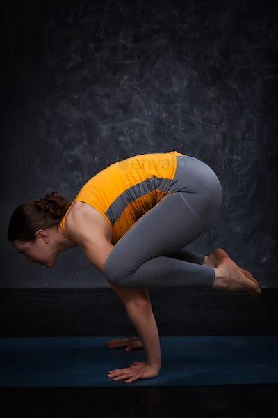 Beautiful sporty fit yogini woman practices yoga asana kakasana