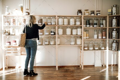 A young happy woman buying groceries in zero waste shop. Copy space.