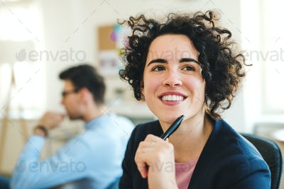 A portrait of young businesswoman with colleagues in a modern office.