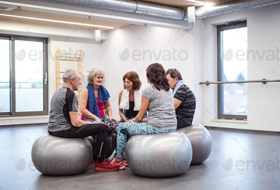 A group of seniors in gym resting after doing exercise on fit balls, talking.