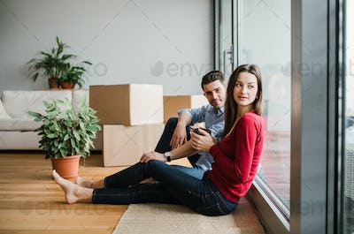 Young couple with cardboard boxes moving in a new home, sitting on a floor.