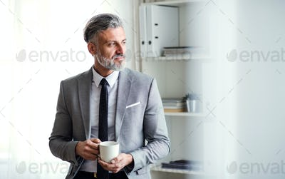A mature businessman standing in an office, holding a cup of coffee. Copy space.