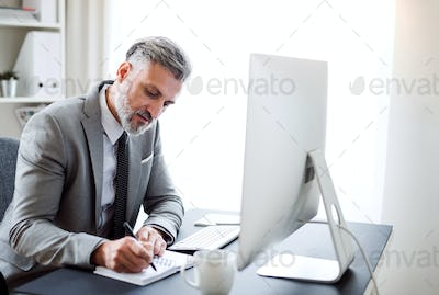 Businessman with computer sitting at the table in an office, making notes.
