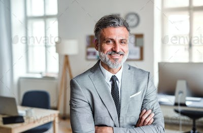 Mature businessman standing in an office, arms crossed.