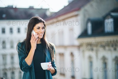 Young businesswoman with smartphone standing on a terrace outside an office in city.