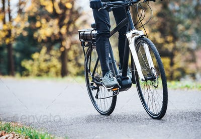 An unrecognizable man on electrobike cycling outdoors on a road in park.