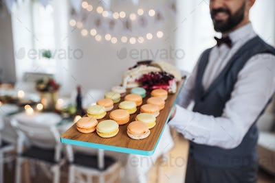 Midsection of man standing indoors in a room set for a party, holding a tray with biscuits.