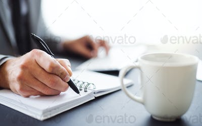 A midsection of businessman sitting at the table in an office, making notes.