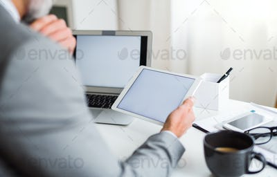 A midsection of businessman sitting at the table, using tablet. Copy space.
