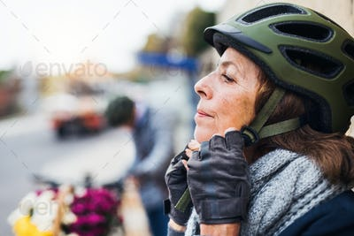 Active senior woman standing outdoors in town, putting on a bike helmet. Copy space.