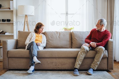 A senior couple sitting on a sofa at home, having an argument.