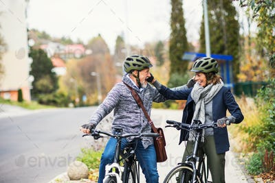 Active senior people with electrobikes greeting outdoors on a road in town.