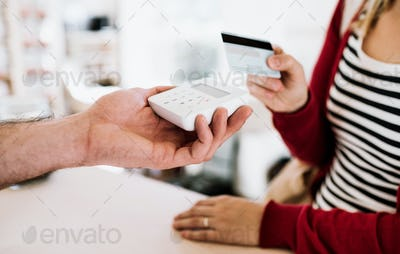 Customer and shop assistant making contactless payment using credit card in a shop.