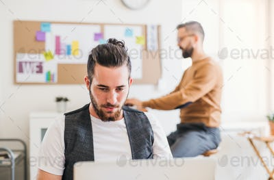 Two young male businesspeople with computer working in a modern office.
