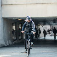 Male bicycle courier delivering packages in city. Copy space.