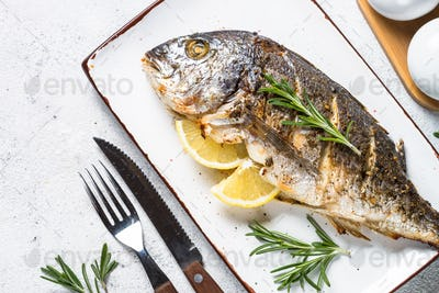 Baked dorado fish with lemon and rosemary top view.