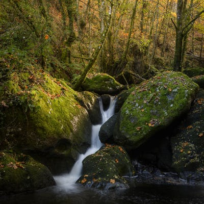 A waterfall rushes between huge boulders