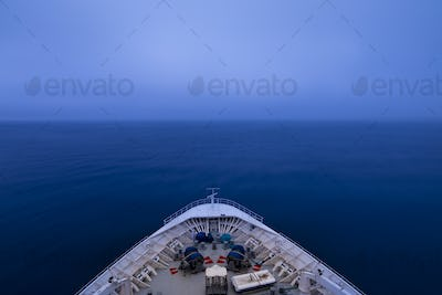 POV shot of bow of a ship sailing into a fog bank in pre dawn ho